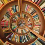 Ein Bücherregal mit verschiedenen Büchern, perspektivisch verzerrt.